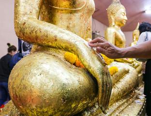Women put gold leaf onto the buddha statue to gild