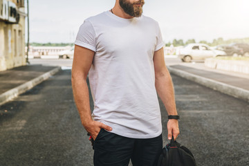 Summer day. Front view. Young bearded millennial man dressed in white t-shirt is stands on city street. Mock up. Space for logo, text, image. Instagram filter, film effect, bokeh effect.
