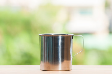 Stainless cup on wooden table.