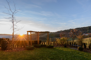 Bright golden sunrise on a winter morning with a blue sky looking through a rose pergola towards the horizon to the sun and sun rays over hills, valleys and idyllic farmland