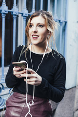 Young blonde woman chatting with her mobile phone in Madrid streets, Spain