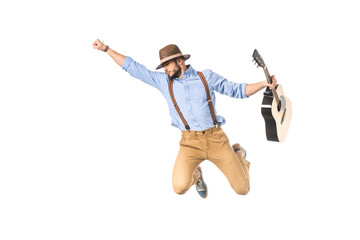 young musician in hat holding guitar and flying with raised hand isolated on white