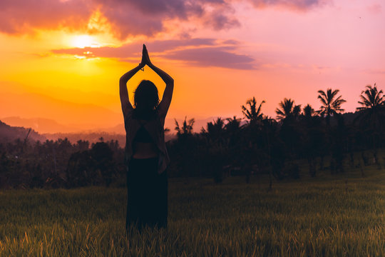 Silhouette meditation yoga woman amazing sunset,Bali,Indonesia.Silhouette of a meditating girl against the background of a magical sunset in a rice field and with coconut palms.Unity of man and nature