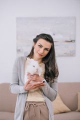 attractive woman holding white rabbit and looking at camera indoors