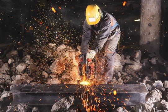 Construction worker cutting an iron beam.