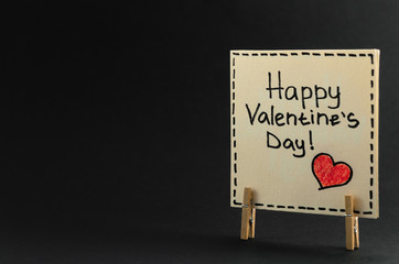 The sticker with the greeting happy Valentines day on the clothespin on a dark background.