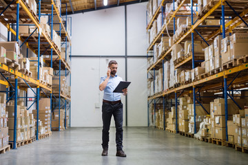 Warehouse worker or supervisor with a smartphone.