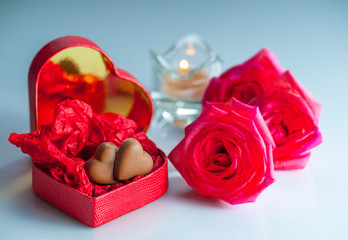 Romantic scenery with red heart-shaped box with chocolate hearts , rose flowers and a candle.