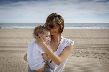 Madre joven en la playa con su hija
