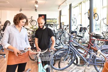 Frau und Verkäufer im Fahrradladen - Kauf eines Rades mit professioneller Beratung //