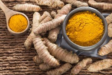 Turmeric powder in the bowl and organic roots - Curcuma longa