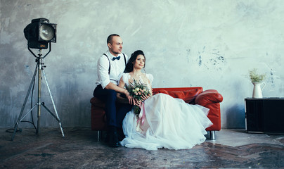 Wedding couple indoors is hugging each other. Beautiful model girl in white dress. Man in suit. Beauty bride with groom on sofa