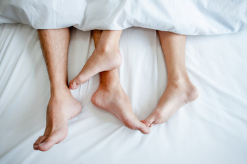 Love lying in bed in hotel,embracing on white sheets, close up legs.