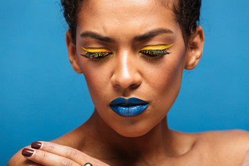 Closeup stylish photo of uptight mixed-race woman with trendy makeup expressing frustration and looking down, isolated over blue wall