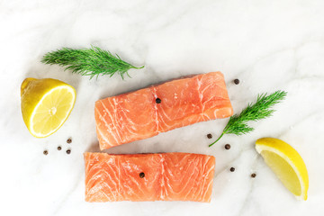 Slices of salmon on white with lemons, dill, and copyspace