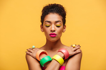Closeup photo of peaceful mulatto woman with closed eyes and pink lipstick posing on camera with crossed hands on shoulders, over yellow wall