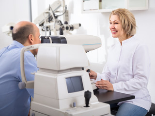 Mature optician examinating eyesight