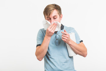Young man has a runny nose on white background