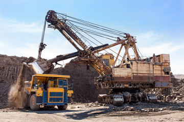 Excavator loading yellow dump truck