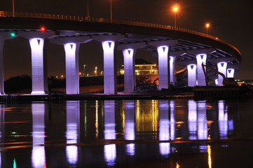 A brightly lit bridge is shown at light reflecting on the water.
