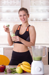 Girl holding bottle with green smoothie in kitchen
