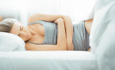 Donna con dolori, mal di stomaco, a letto