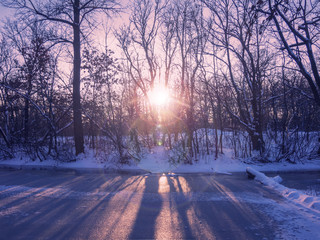 Sunset on the frozen forest lake in winter.