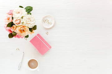 Flat lay home office desk. Female workspace with pink and beige roses flowers bouquet, coffee and chocolates on white wooden background. Top view feminine background.