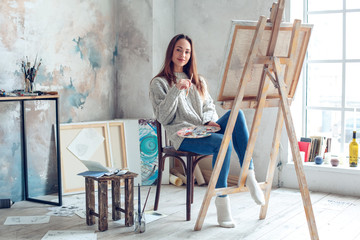 Young woman artist painting at home creative holding brush