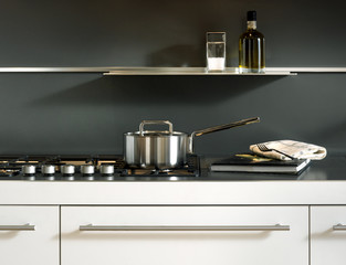 steel pot on a gas cooking top with grey wall and white drawers