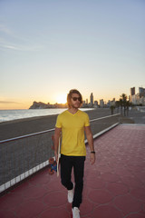 Casual young man with skateboard at sunset