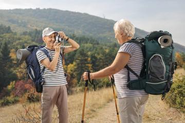 Elderly male hiker taking a picture of an elderly female hiker
