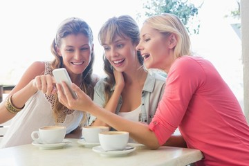 Happy friends having coffee together looking at phone