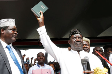 Kenyan opposition leader Raila Odinga of the National Super Alliance (NASA) holds a bible as he takes a symbolic presidential oath of office in Nairobi, Kenya