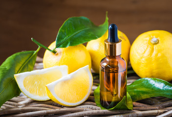 Citrus bergamot essential oil, aromatherapy or natural organic beauty cosmetic oil. Bottle of essential oil on rustic wood background.
