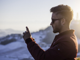 Handsome young man outdoor in winter fashion using smartphone to take photo of the landscape, wearing black coat and woolen scarf