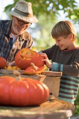 a man teaching his son how to carve a pumpkin for halloween.