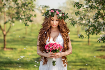 Beautiful bride with long hair in a flowered garden. A spring wedding.