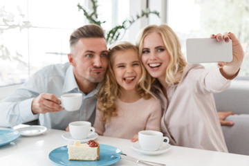happy young family taking selfie and making grimaces at restaurant