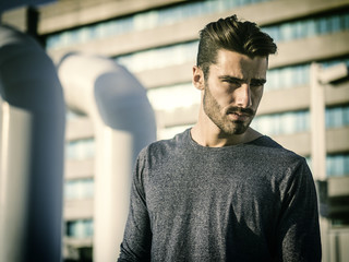 Attractive young bearded man portrait in urban environment