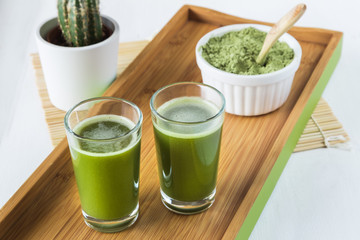 Two wheatgrass shots with powdered wheatgrass and wooden spoon