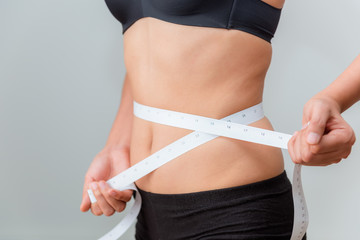 Portrait of hands measuring waist with a tape, Healthy and diet concept