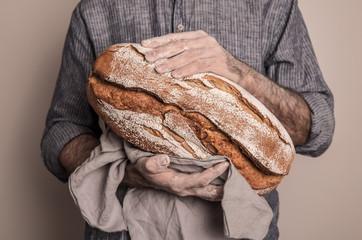 Rustic crusty loaf of bread in baker man's hands
