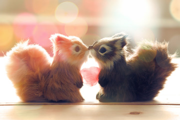 Two squirrels are kissing and hold heart candy on wood plate with abstract glow bokeh background.