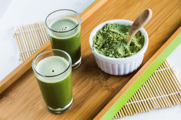 Wheatgrass shots with powdered wheatgrass and wooden spoon