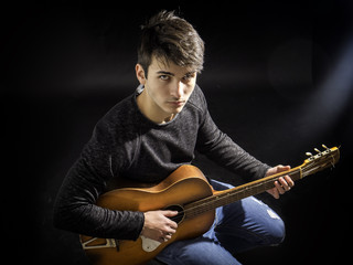 Portrait of hipster young man or teen playing guitar against black background, in studio shot