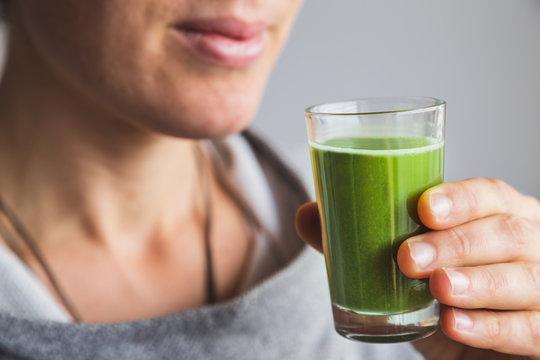 Woman holding shot of wheatgrass juice