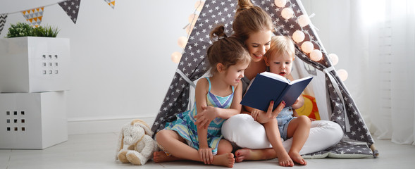 family mother reading to children book in tent at home