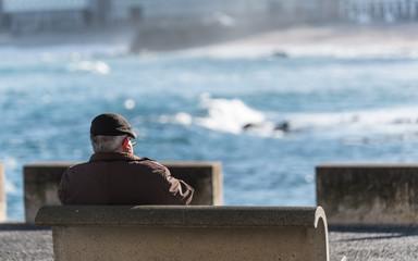 Elderly man sitting on a bench smoking a  cigar
