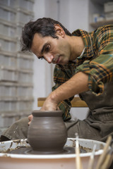 Artist makes clay pottery on a spin wheel in workshop